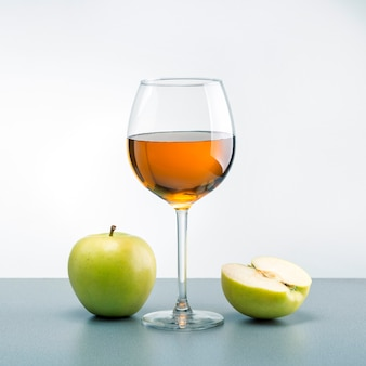 Um copo de suco de maçã com maçãs verdes em cima da mesa.