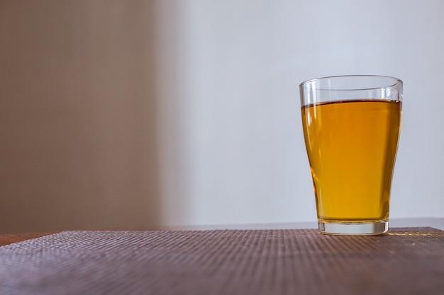 Um copo de suco de maçã está sobre a mesa