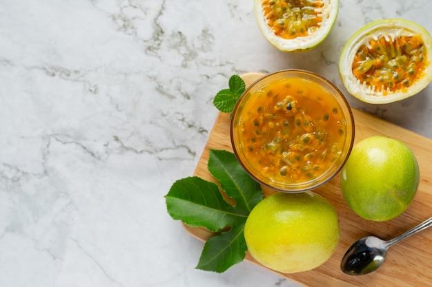 Um copo de suco de maracujá e maracujá fresco cortado ao meio em uma tábua de madeira