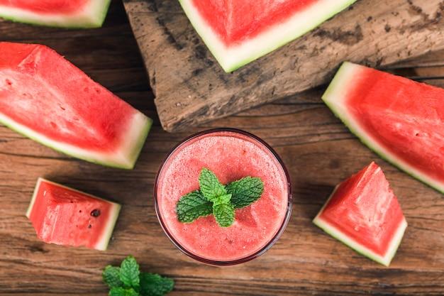 Um copo de suco de melancia em um fundo de madeira