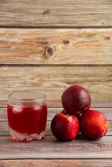 Um copo de suco de pêssego com cubos de gelo e frutas ao redor