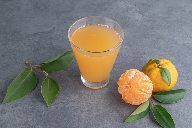 Um copo de suco de tangerina com folhas