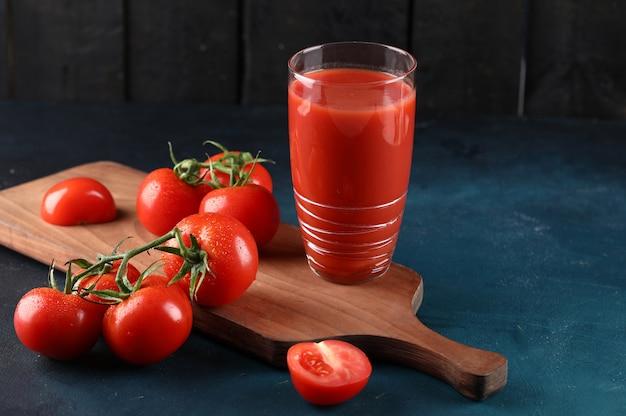 Um copo de suco de tomate e alguns tomates frescos na placa de madeira.