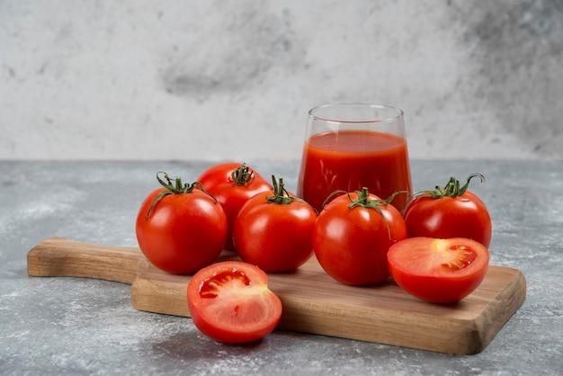 Um copo de suco de tomate em uma placa de madeira.