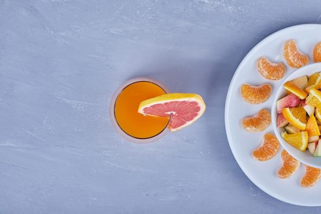Um copo de suco de toranja com salada de frutas.