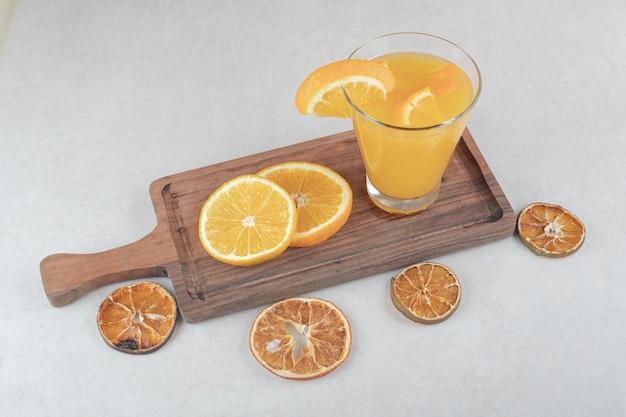 Um copo de suco e rodelas de laranja na tábua de madeira