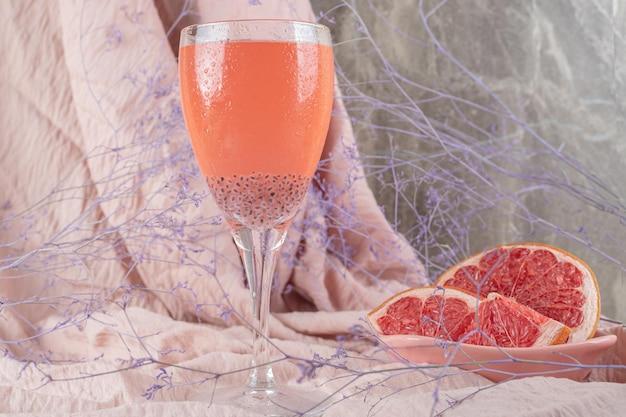 Um copo de suco e toranja fresca em um pano rosa.