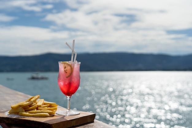 Um copo de suco ou um coquetel com prato de batatas fritas no almoço em uma bela vista do mar.