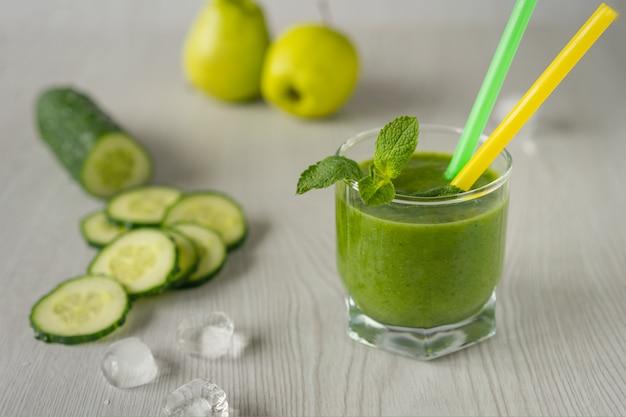 Um copo de suco vegetal verde sobre um fundo claro de madeira, ao lado de um pepino e maçã