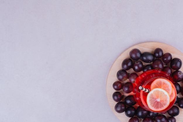 Um copo de suco vermelho com cereja em uma placa de madeira