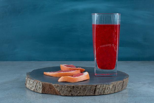 Um copo de suco vermelho com fatias de toranja.