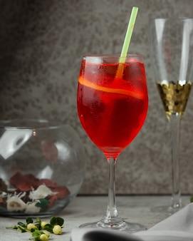 Um copo de suco vermelho com uma fatia de laranja