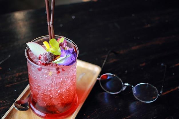 Um copo de suco vermelho e frutas na mesa.