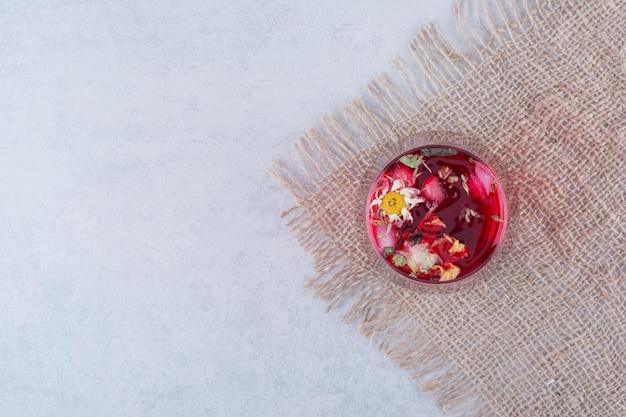 Um copo de suco vermelho na serapilheira com flores.
