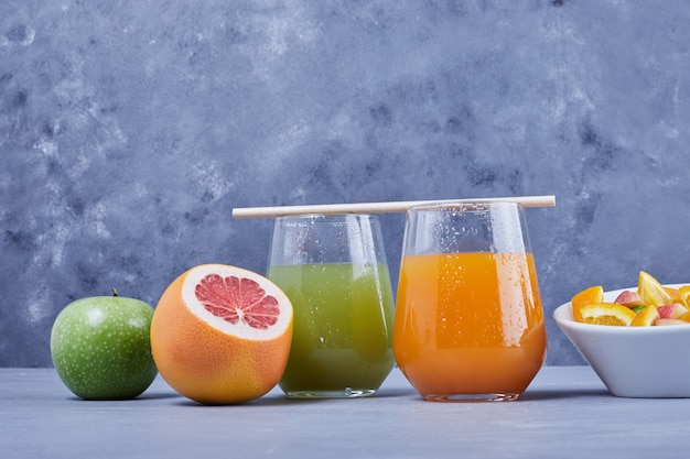 Um copo de tangerina e suco de maçã.