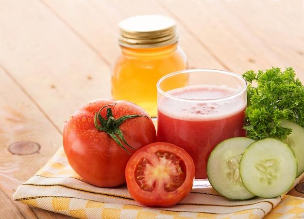 Um copo de tomate fresco mistura suco de pepino com ingredientes