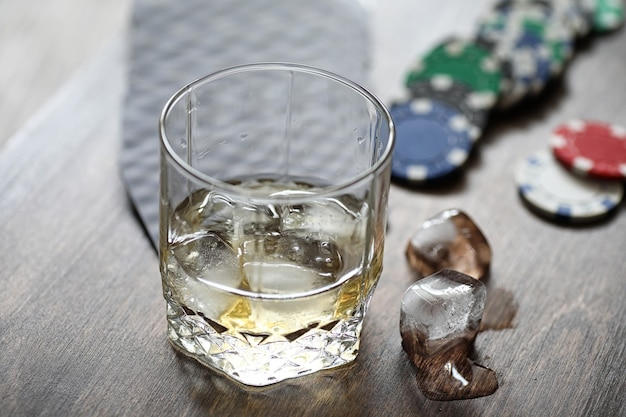 Um copo de uísque com gelo na mesa de jogo com fichas e cartas