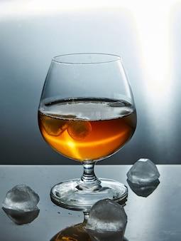 Um copo de uísque com gelo.