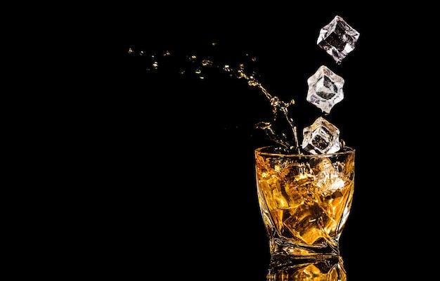 Um copo de uísque com respingos do cubo de gelo