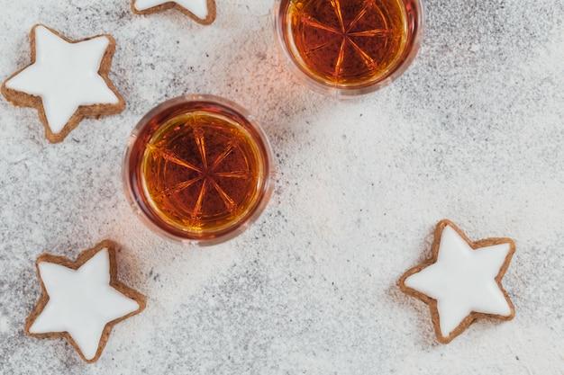 Um copo de uísque ou bourbon, biscoitos estrela e decoração em branco
