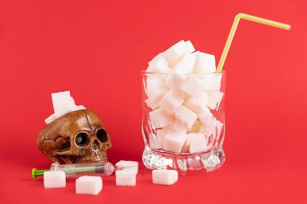Um copo de vidro branco com um canudo, cheio de cubos brancos de açúcar refinado e uma caveira humana sobre um fundo vermelho. copie o espaço.