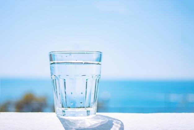 Um copo de vidro cheio de água limpa fica em uma praia de areia junto ao mar. estilo de vida saudável.