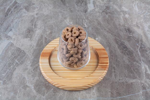 Um copo de vidro cheio de anéis de cereais de chocolate em uma placa de madeira.