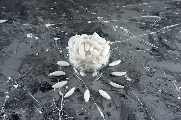 Um copo de vidro cheio de balas brancas de menta em uma superfície de mármore