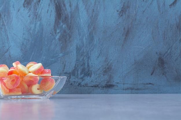 Um copo de vidro cheio de balas coloridas de gelatina de frutas