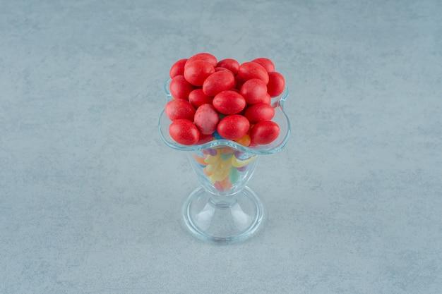 Um copo de vidro cheio de doces de feijão colorido em um fundo branco. foto de alta qualidade