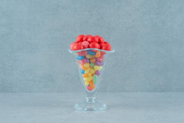 Um copo de vidro cheio de doces de feijão coloridos em uma superfície branca