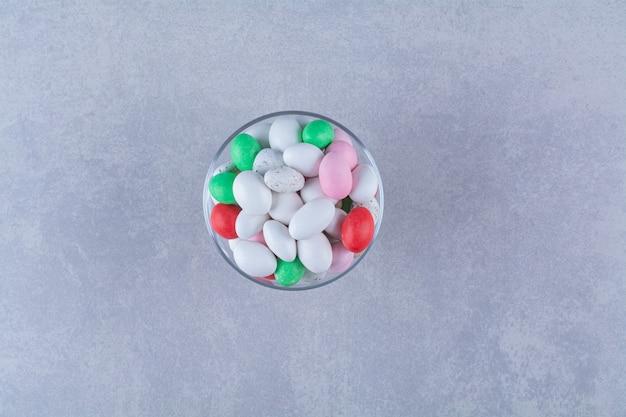 Um copo de vidro cheio de doces de feijão coloridos. foto de alta qualidade