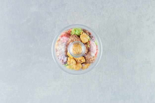 Um copo de vidro cheio de pipocas doces multicoloridas.