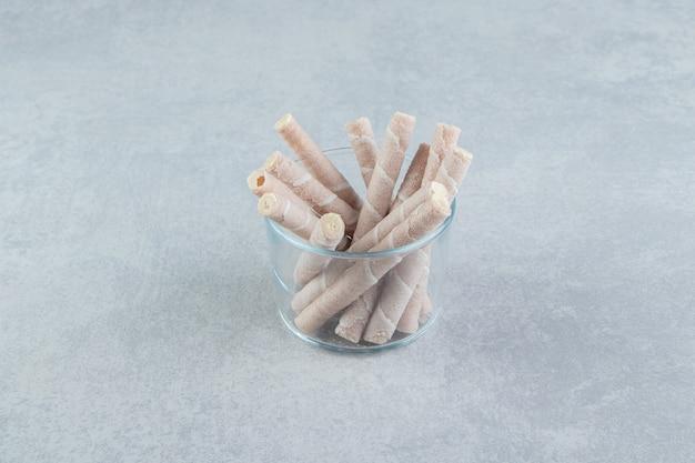 Um copo de vidro cheio de rolos de waffle crocantes. Foto gratuita