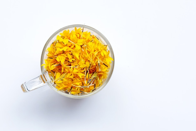 Um copo de vidro com pétalas de flores de calêndula. conceito de chá de ervas de flores.