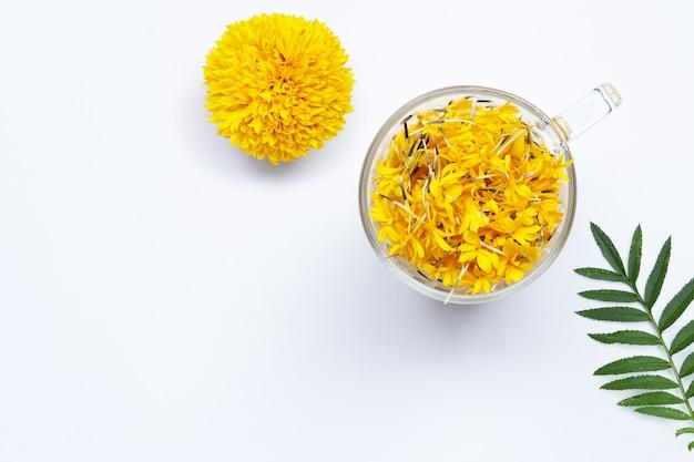 Um copo de vidro com pétalas de flores de calêndula em fundo branco. conceito de chá de ervas de flores.