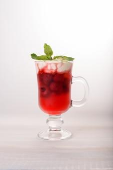 Um copo de vidro com uma bebida fria de framboesa com chantilly e hortelã por cima.