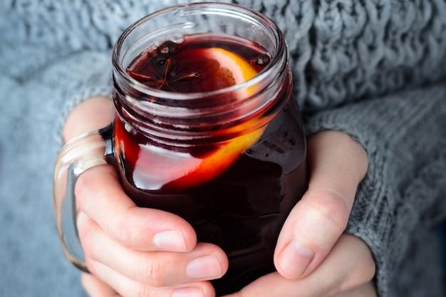 Um copo de vidro com vinho quente com um pedaço de laranja e uma estrela de anis em suas mãos