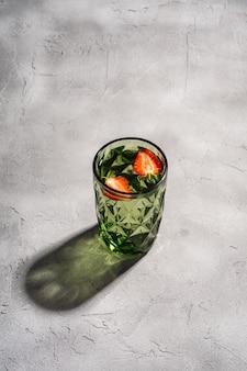 Um copo de vidro geométrico verde com frutas frescas e morango com raios de luz sombra colorida na superfície de concreto de pedra