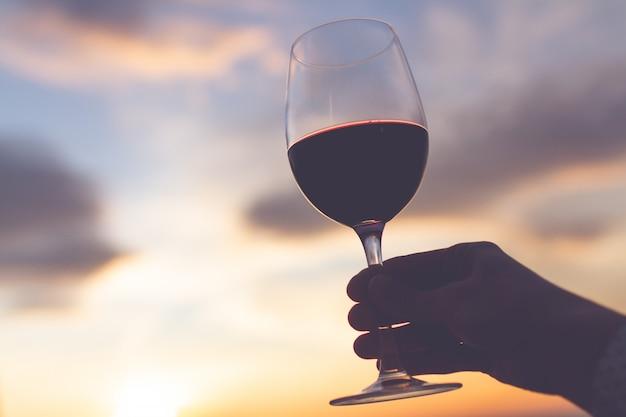 Um copo de vinho ao pôr do sol à noite.
