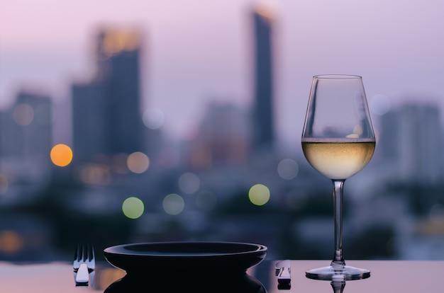 Um copo de vinho branco com prato com as luzes da cidade de fundo.