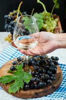 Um copo de vinho branco com um cacho de uvas vermelhas ao redor.