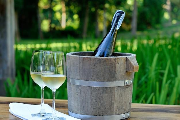 Um copo de vinho branco e garrafa de vinho no balde de gelo na mesa de madeira