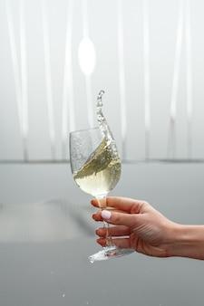 Um copo de vinho branco na mão de uma mulher