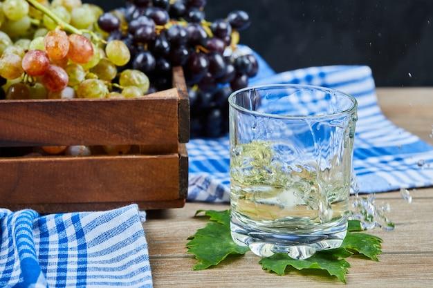 Um copo de vinho branco na mesa de madeira com uvas.