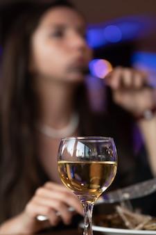 Um copo de vinho branco - pernas de mulheres sexy no fundo. foto de alta qualidade