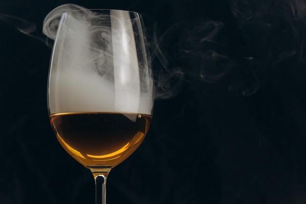 Um copo de vinho branco sobre um fundo preto. a fumaça do cachimbo de água envolve o copo.