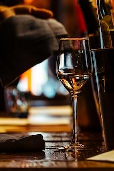 Um copo de vinho na mesa de madeira do restaurante.