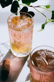 Um copo de vinho rosa em um copo de cristal em mármore, hera verde e sol brilhante