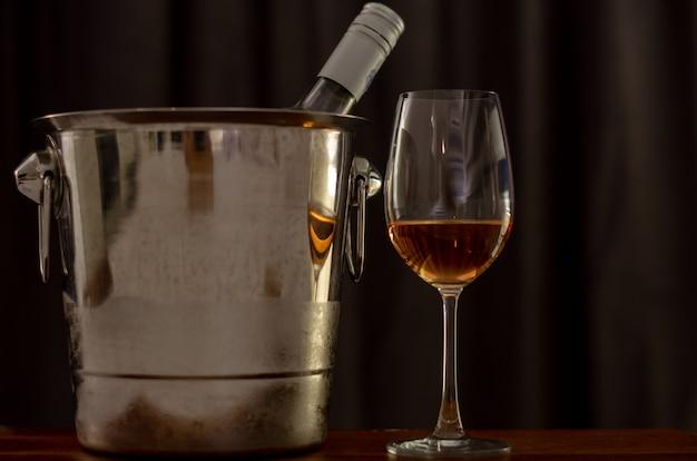 Um copo de vinho rose na mesa de madeira com uma garrafa no balde refrigerador de vinho.